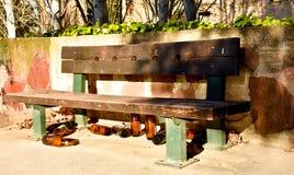 许多大橙色瓶啤酒由玻璃制成完全地空在公园由于某人在留下他们前喝了时间 免版税库存图片