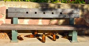 许多大橙色瓶啤酒由玻璃制成完全地空在公园由于某人在留下他们前喝了时间 库存照片