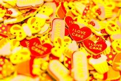 许多顶视图描述心脏、蝴蝶和杯形蛋糕的五颜六色的泡沫贴纸 在两心脏的焦点 夏天或喜悦概念 免版税库存照片