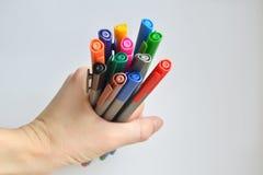 设置彩虹上色了举行在妇女的手上的笔,在白色背景 库存照片