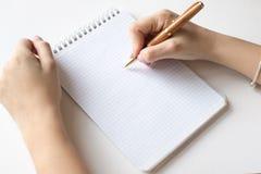 设计观念-螺纹笔记本、白页和笔,妇女在大模型的白色背景隔绝的举行笔顶视图  免版税库存图片