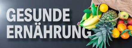 词GESUNDE ERNAHRUNG,德语为健康吃或健康营养,用在纸袋的新鲜水果 免版税库存照片