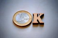 词OK由木信件和欧元硬币做成在灰色背景 金融投资或交易的金钱概念 免版税库存照片