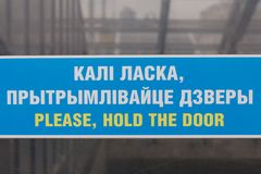 请,拿着门签字在英语和白俄罗斯语的语言 免版税库存图片