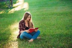 读书的俏丽的白肤金发的年轻女人在公园 免版税图库摄影