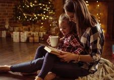 读她的女儿的母亲一本书安静的,eveneing的冬天 免版税库存照片