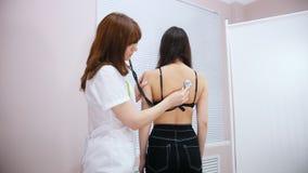 诊所 医生与听诊器一起使用 检查后面 股票视频