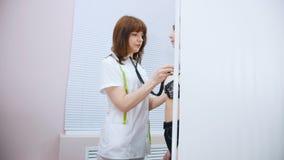 诊所 医生与听诊器听力患者的心脏拍打一起使用 股票录像