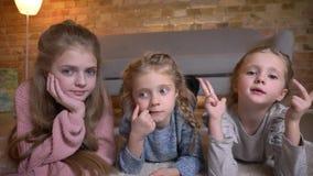 说谎在地板上和镇静地观看入照相机的三个小白种人女孩画象在舒适家庭环境 影视素材