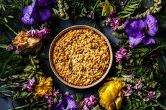 说谎在灰色背景的明亮的花和苹果饼花束  平的位置 顶视图 免版税库存照片