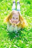 说谎在草的女孩在grassplot,绿色背景 孩子享受春天晴朗的天气,当说谎在草甸时 全盛时期 免版税库存图片