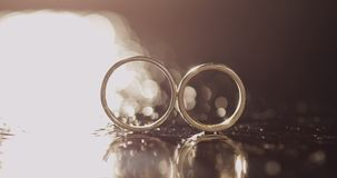 说谎黑暗的水表面上的结婚戒指发光与光 关闭宏指令 在水对的圆环 ReflectionWedding敲响说谎的o 影视素材