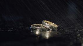 说谎黑暗的表面上的结婚戒指发光与宏指令的轻的关闭 3d背景回报飞溅空白的水 股票录像
