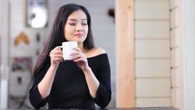谦虚可爱的亚裔少女放松的在家坐在桌和饮用的热的饮料上 股票视频