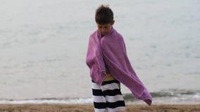 调查照相机,男孩的单独毛巾立场的疲倦的哀伤的难民男孩设法保持温暖 免版税库存图片