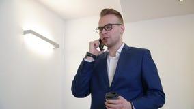 谈话在手机和拿着咖啡杯的英俊的商人在办公室 股票视频