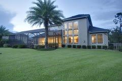 豪华家庭外部建筑黄昏黎明夜草坪日落内部的光转动在水平的取向风景 库存图片