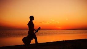 走与在海滩的吉他的少女在日落 股票视频
