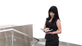 走在办公室的年轻可爱的妇女,读在笔记本的信息 股票录像
