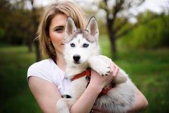 走在公园的女孩和她的狗爱斯基摩 免版税库存图片
