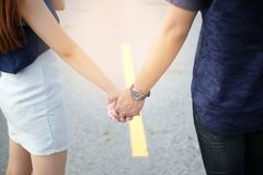 走在路的年轻亚洲夫妇,当握充满纯净的爱时的手 库存照片