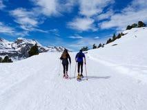 走在雪靴和棍子杆的旅行者夫妇在一座多雪的山的道路的冬天的白雪 免版税库存图片
