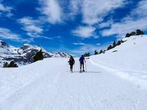 走在雪靴和棍子杆的旅行者夫妇在一座多雪的山的道路的冬天的白雪 库存图片