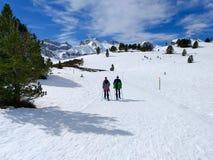 走在雪靴和棍子杆的旅行者夫妇在一座多雪的山的道路的冬天的白雪 免版税库存照片