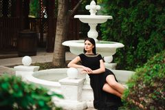 走和摆在短的黑礼服的年轻美丽的时髦的女孩在城市在喷泉附近 室外夏天画象  免版税库存照片