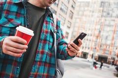 走通过有杯子的大城市街道热的咖啡和使用智能手机的时髦人为与他的朋友的录影链接 免版税库存照片