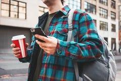 走通过有杯子的大城市街道热的咖啡和使用智能手机的时髦人为与他的朋友的录影链接 免版税库存图片