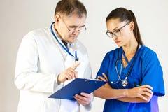 资深医生解释给年轻女人医生如何规定治疗 免版税图库摄影