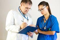 资深医生谈话与同事和谈论患者的治疗 库存照片