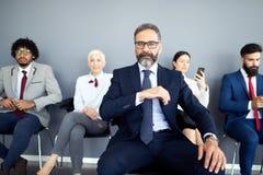 资深商人画象作为领导的在现代明亮的办公室内部 免版税库存图片