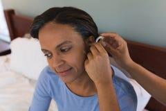 资深由女性医生的妇女适合的助听器在卧室在家 免版税库存图片