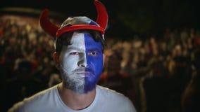 足球迷在体育场内站立和严密地观看与油漆面孔的足球 股票录像