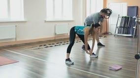 超重男性和女性教练员与完善的身体烧伤卡路里由锻炼 从运动女孩的个人训练为 股票录像