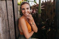 趋向成套装备的迷人的可爱的欧洲妇女有被晒黑的皮肤的微笑对照相机和享受的夏日在热带 库存图片