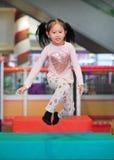 跳跃在户内操场的愉快的矮小的亚洲儿童女孩戏剧 库存照片