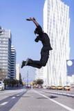 跳跃在都市背景中的一个年轻黑人佩带的便服的侧视图 生活方式概念 千福年的非洲人 免版税库存图片