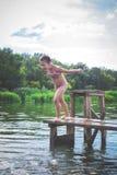 跳跃船坞的小逗人喜爱的女孩入一条美丽的河在日落 库存图片
