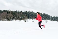 跑在戴着在多雪的天气的冬天山的雪的年轻女人温暖的衣物手套 免版税库存照片