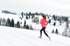 跑在戴着在多雪的天气的冬天山的雪的年轻女人温暖的衣物手套 库存照片