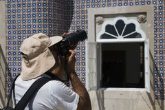 辛特拉,葡萄牙,2018年8月25日:盖帽照片的一个人马赛克 他看反光镜并且握他的在的手指 免版税库存照片