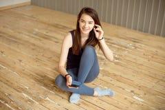 运动服的美丽的运动女孩,坐地板和放松在健身房的健身锻炼以后与电话 免版税库存照片