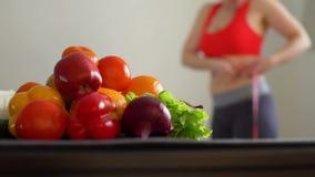 运动的妇女在健康食品附近测量她的腰部 股票录像