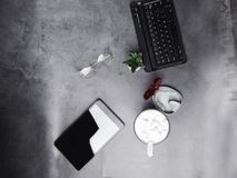 运转的书桌用咖啡,玻璃,牙直线对准器,在具体书桌上的笔记本 免版税库存照片