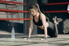 进行在地板上的运动的女孩俯卧撑 有吸引力的妇女年轻人 库存照片