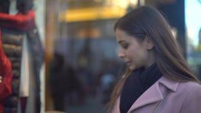 花姑娘在商店窗口里的看衣物,有没有足够的金钱 股票视频