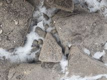 花岗岩石头在雪背景纹理的,在山河,积雪的土地附近的多雪的石头 免版税库存照片
